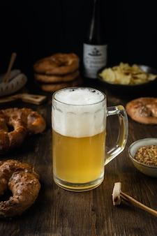 プレッツェル、ソーセージ、素朴な木製のテーブルで軽食とビールのグラス