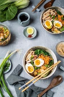チンゲン菜、ニンジン、ライム、ゴマ、鶏肉、卵入りのアジア風ラーメンスープ