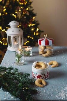 Домашняя рождественская пекарня, ванильное печенье в форме полумесяца со свечами, рождественская елка и боке