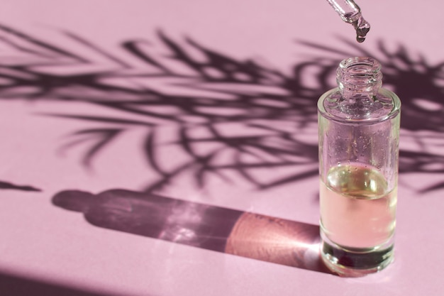 ピペットからガラス瓶に落下する化粧品油または血清