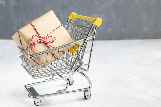 クリスマスセールコンセプト - ペーパークラフトと小さなショッピングカートで赤と白のツイストコード付きギフト。