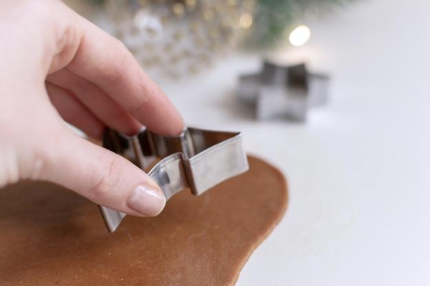 クリスマス料理 - 自家製ジンジャーブレッドクッキーを準備する女性の手の選択と集中