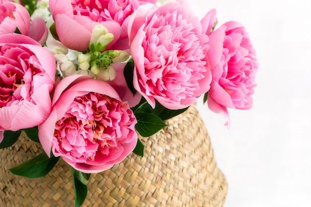 ストローバスケットで美しいピンクの牡丹の花束