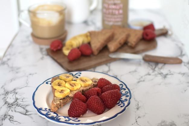 健康的な朝食ピーナッツバターサンドイッチ、バナナ、ラズベリー、