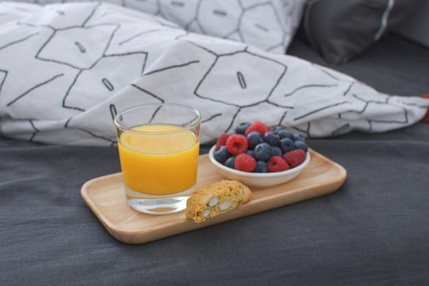 Кровать для завтрака деревянный поднос интерьер раннего утра геометрическая простыня и наволочка ягоды апельсиновый сок печенье