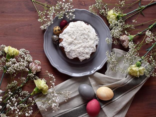 ココナッツシェル、カスミソウの花、クローブのイースターケーキと着色された装飾イースターエッグの選択的な焦点