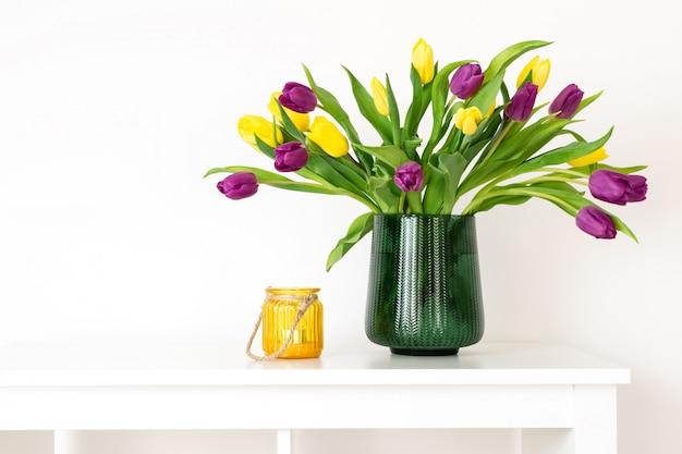 最小限の組成、スカンジナビアの北欧スタイル、家のインテリア、緑の花瓶の母の日チューリップ、黄色のキャンドルホルダー