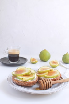 新鮮な緑のイチジクサンドイッチカナッペグレーの素朴なプレートブラックコーヒー