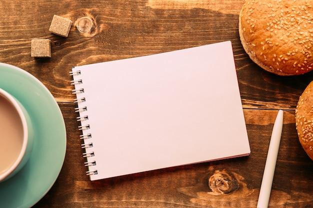 Блокнот с ручкой на столе рядом с какао