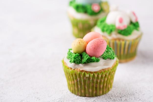 マスチック卵と明るい背景に草のお祝いカップケーキ。イースター休暇の概念。コピースペース