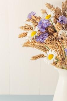 Спелая пшеница в белой вазе на деревянном фоне