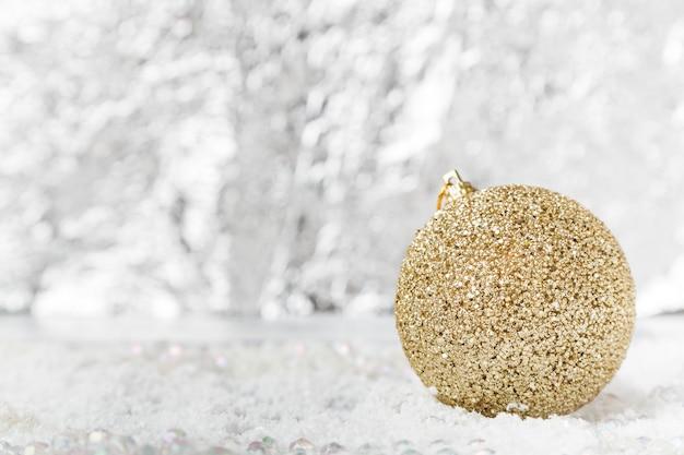 Рождественский золотой шар на снегу