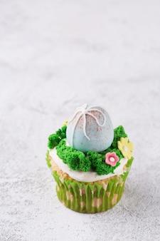 マスティック卵とテーブルの上の草のイースターカップケーキ。イースター休暇の概念。コピースペース