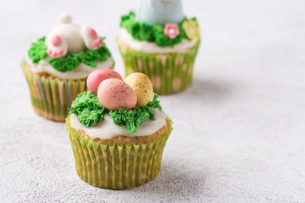 マスティック卵と明るい背景に草でお祝いカップケーキ。イースター休暇の概念。コピースペース