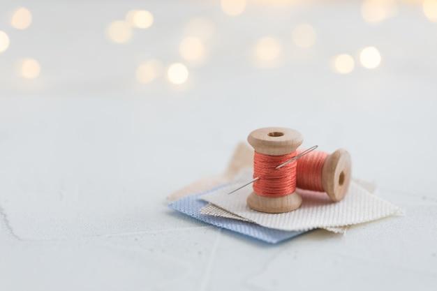 白い背景の上のリネンパックに針でステッチするためのサンゴ色スレッド木製ボビン
