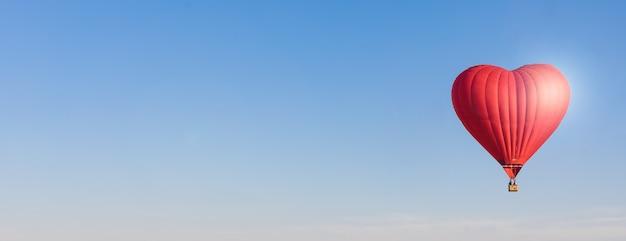 赤いハート形の空気風船、空のバナーで分離