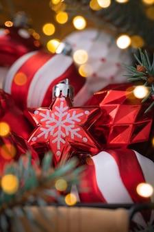 Крупный план рождественских красных и белых стеклянных игрушек в корзине с еловыми ветками