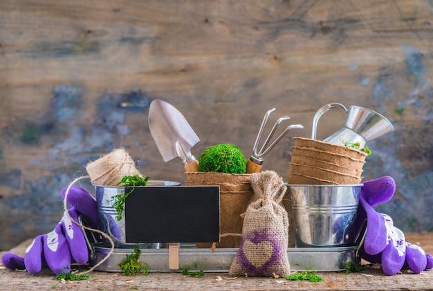 Садовые инструменты, горшки и посуда на деревенском деревянном фоне, с классной доской