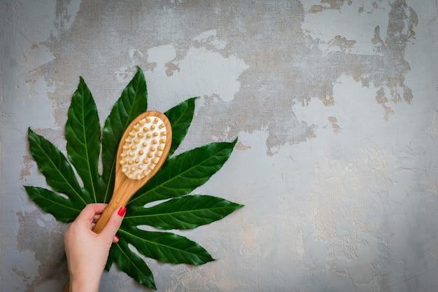 禅デトックス静物-緑の熱帯の葉の背景にボディスパトリートメント竹ブラシ