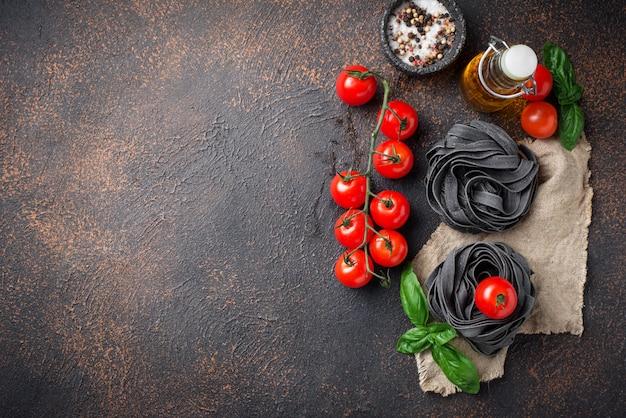 Черные сырые макароны с помидорами и базиликом