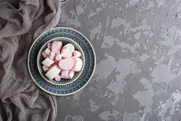 Белые и розовые зефиры на сером фоне бетона. выборочный фокус