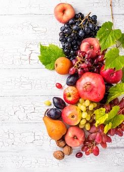 Различные осенние фрукты на белой древесине