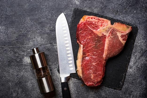 Сырой стейк на косточке на грифельной доске