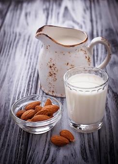 Миндальное молоко и миндаль на деревянном фоне