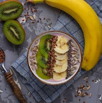 バナナ、キウイ、チア、亜麻、ヒマワリの種のボウルにスムージー
