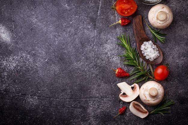 きのこ、トマト、ローズマリー、塩、油。食品の背景
