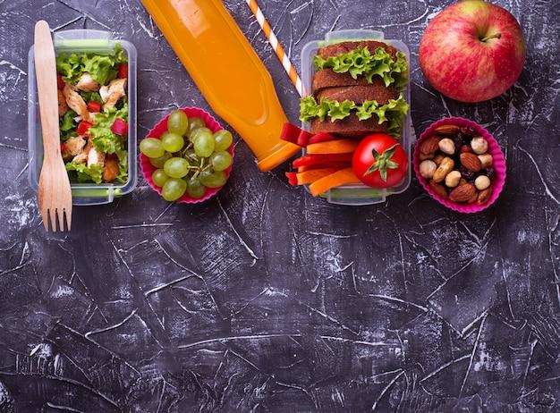 Школьный обед. салат, бутерброды, фрукты и орехи