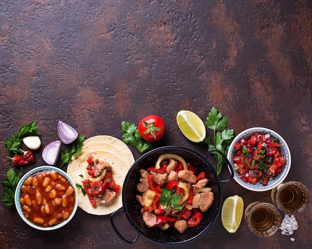 メキシコ料理のコンセプトです。サルサ、トルティーヤ、豆、ファヒータ、テキーラ