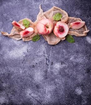 Свежие спелые персики на бетонном фоне
