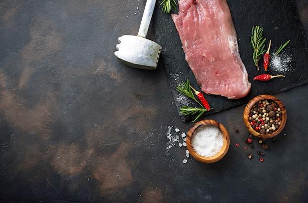 さびた背景にスパイスと生の肉ステーキ