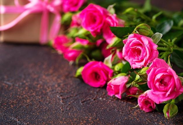 Розовые розы и подарочные коробки с лентами