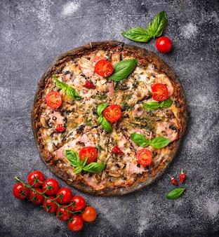 黒い生地のイタリアのピザ。流行の食べ物
