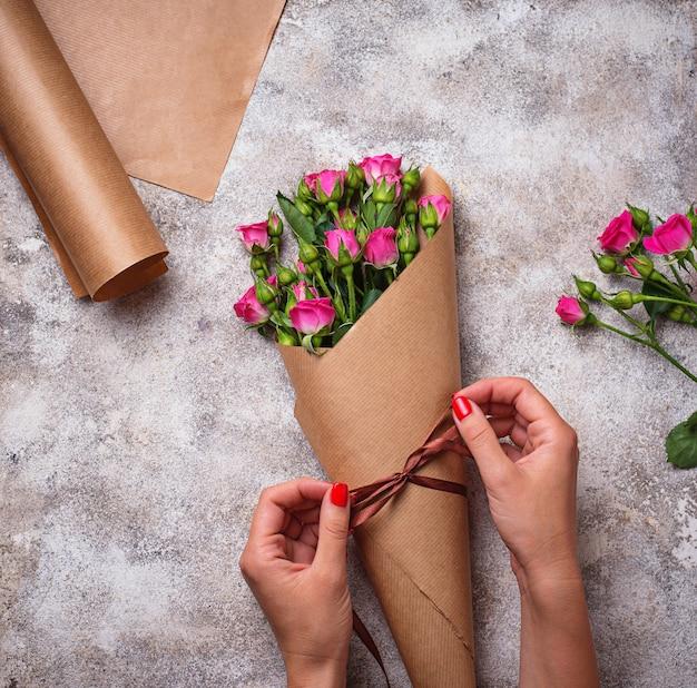 女性の手が紙のバラの花束を包む