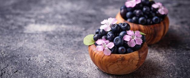 Свежие спелые ягоды черники в деревянной миске