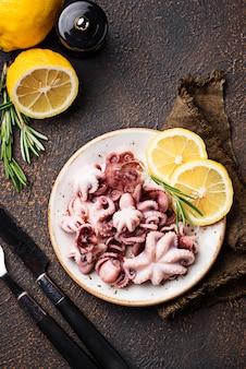 Детский осьминог в тарелке с лимоном и розмарином