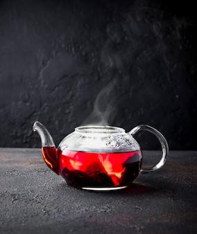 ガラスのティーポットの赤いハイビスカスの花茶