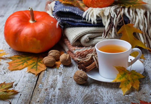 葉、カボチャ、紅茶のカップの秋の背景