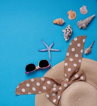 Соломенная шляпа и ракушки на синем фоне