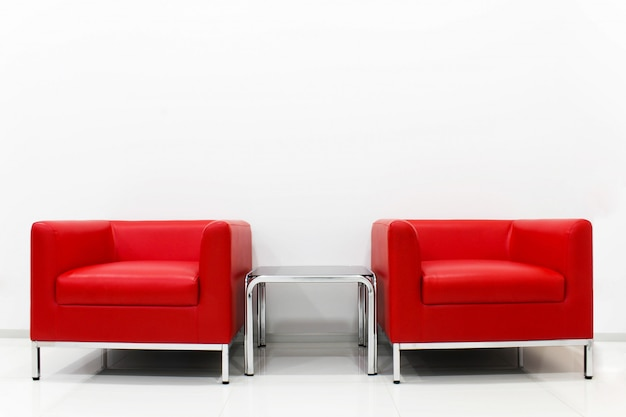 家具セットの赤いソファは白いセメントの壁の隣にあります。