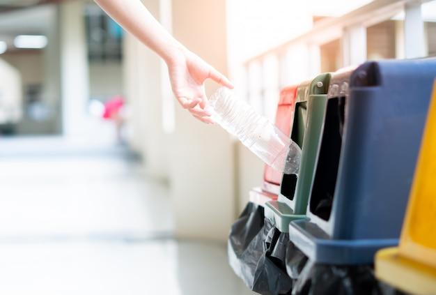 ボトルを持っている手の女性がそれをゴミ箱に投げています。