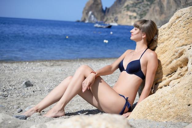 美しい若い女性はビーチで日光浴します。
