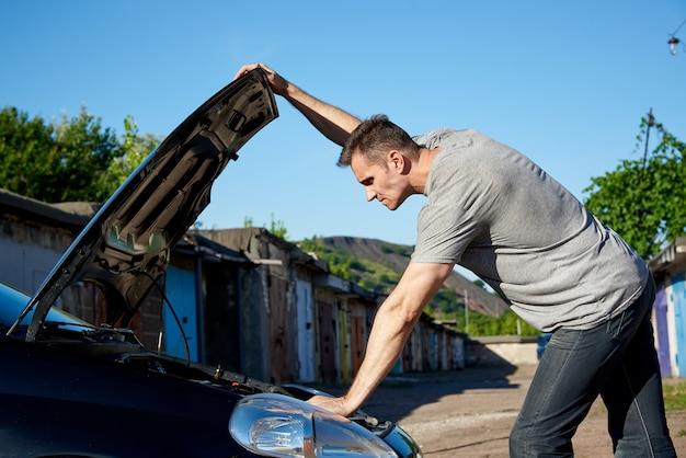 フードが開いている自動車の近くの若い男。