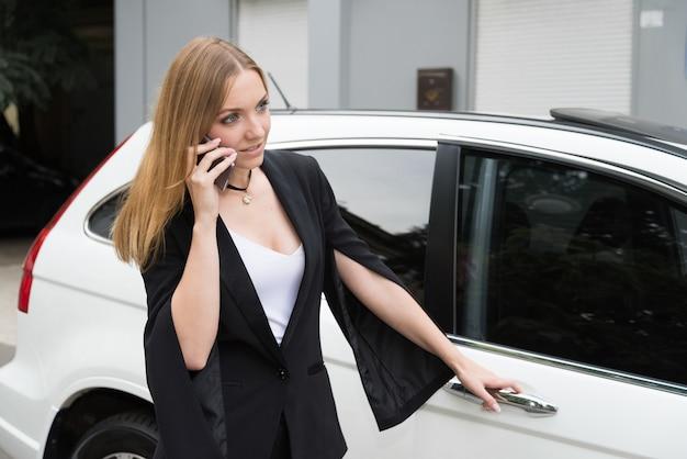 若い女性は車の近くに電話で話しています。