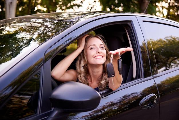 自動でキーを持つ幸せな若い女性。