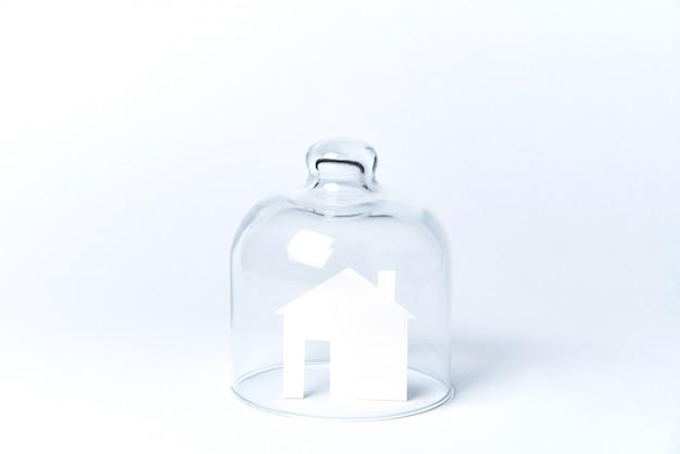 Дом из белой бумаги под стеклом