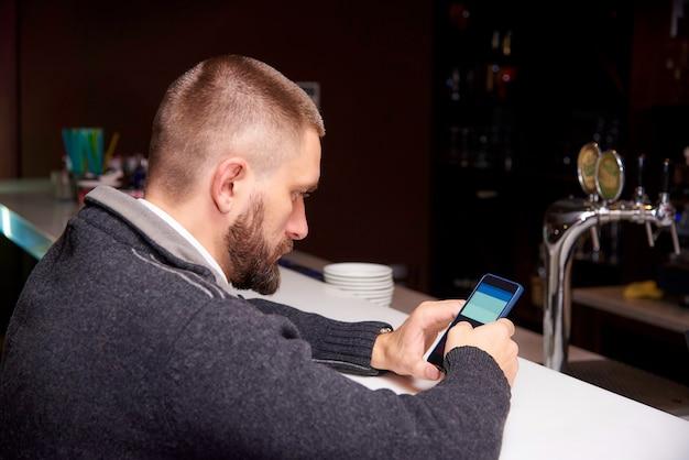バーで携帯電話を持つ若者